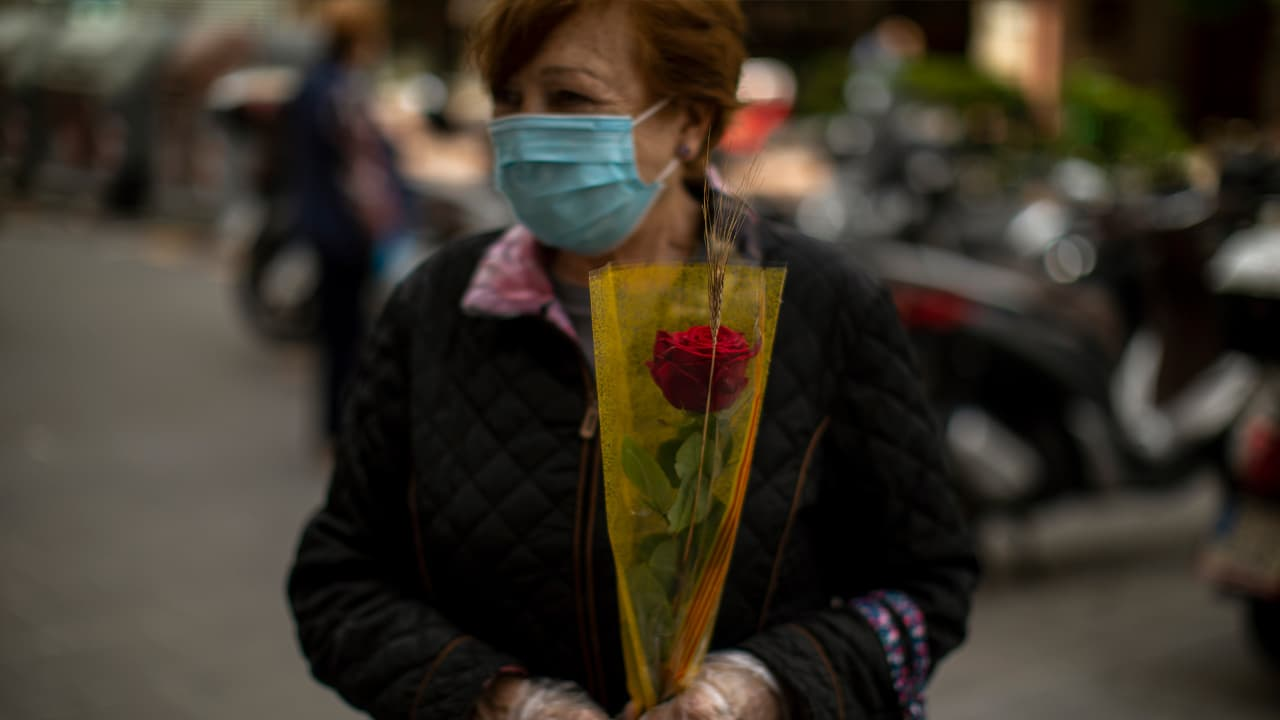 Photo of a woman wearing a face mask and holding a rose in Barcelona