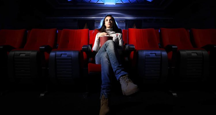 Photo of a woman who is the only one at a movie theateritting in