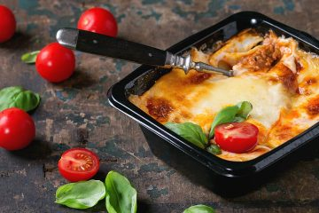Photo of baked lasagna in a to-go container