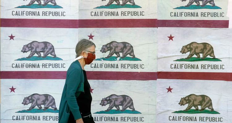 Photo of a woman wearing a mask walking past California flags