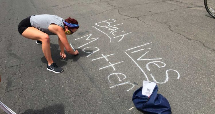 "Photo of a protester writing ""Black Lives Matter"" in chalk on a downtown street in Fresno, California."