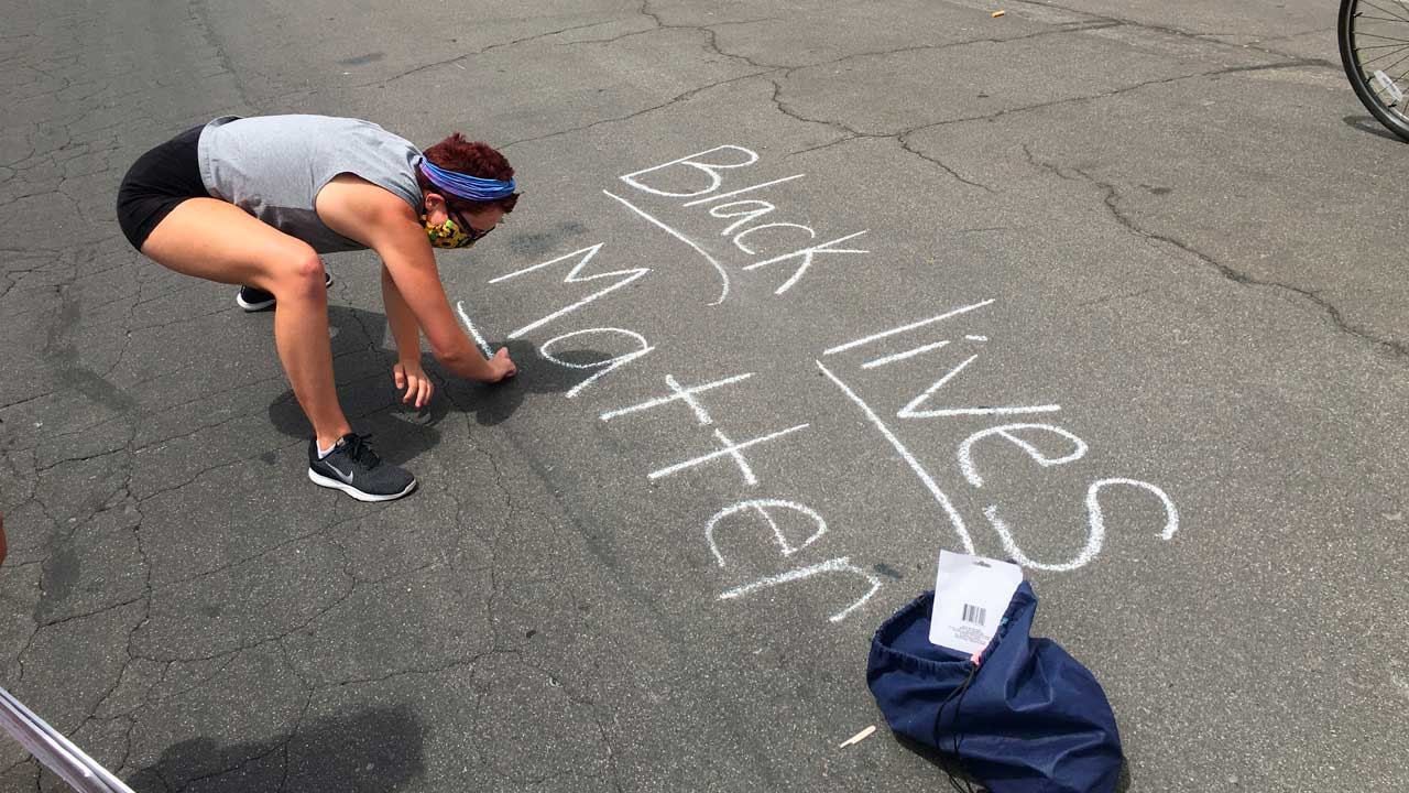 """Photo of a protester writing """"Black Lives Matter"""" in chalk on a downtown street in Fresno, California."""