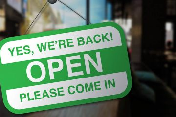 Photo of a sign on a business door welcoming customers back