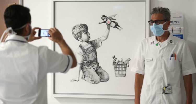 Photo of health care workers in front of a new artwork by Banksy