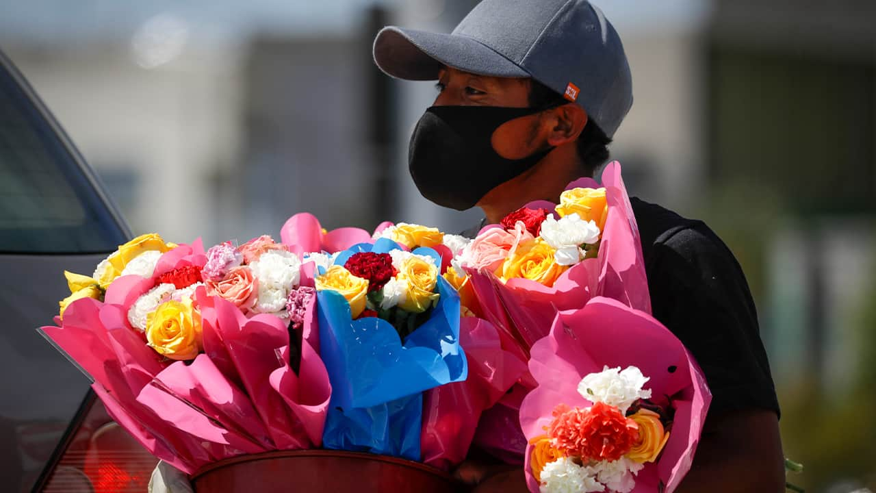 Photo of a man selling flowers and wearing a face mask