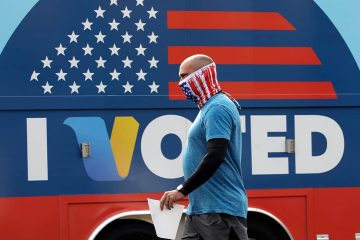 Photo of a man walking past an I Voted sign