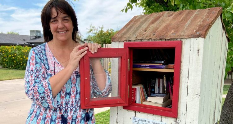 Photo of a Kerri Kaplan next to her small library