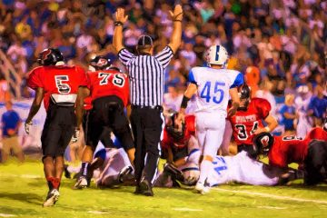 Photo of a referee signaling a touchdown in a high school football game