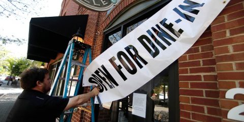 Photo of Jason Godbey hanging a dine-in sign