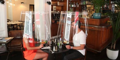 Photo of people dining with plastic shields