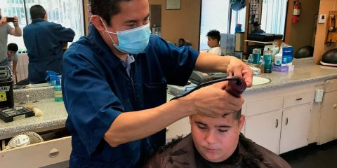 Image of a Madera, California barber wearing a mask while cutting a customer's hair