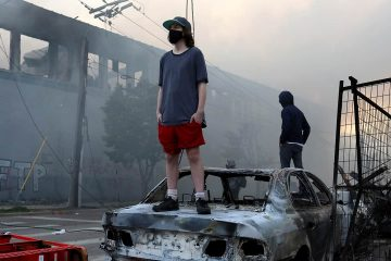 Photo of a man standing on a burnt car