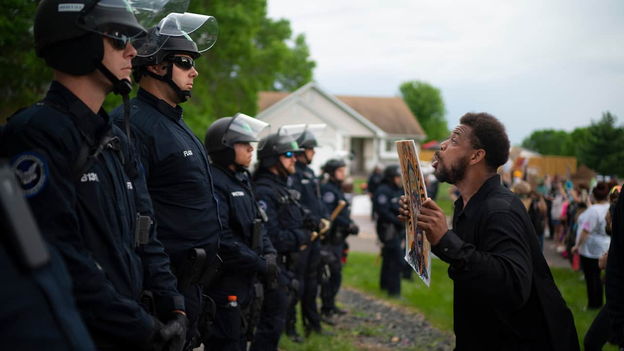 Photo of a man standing in front of a line of cops