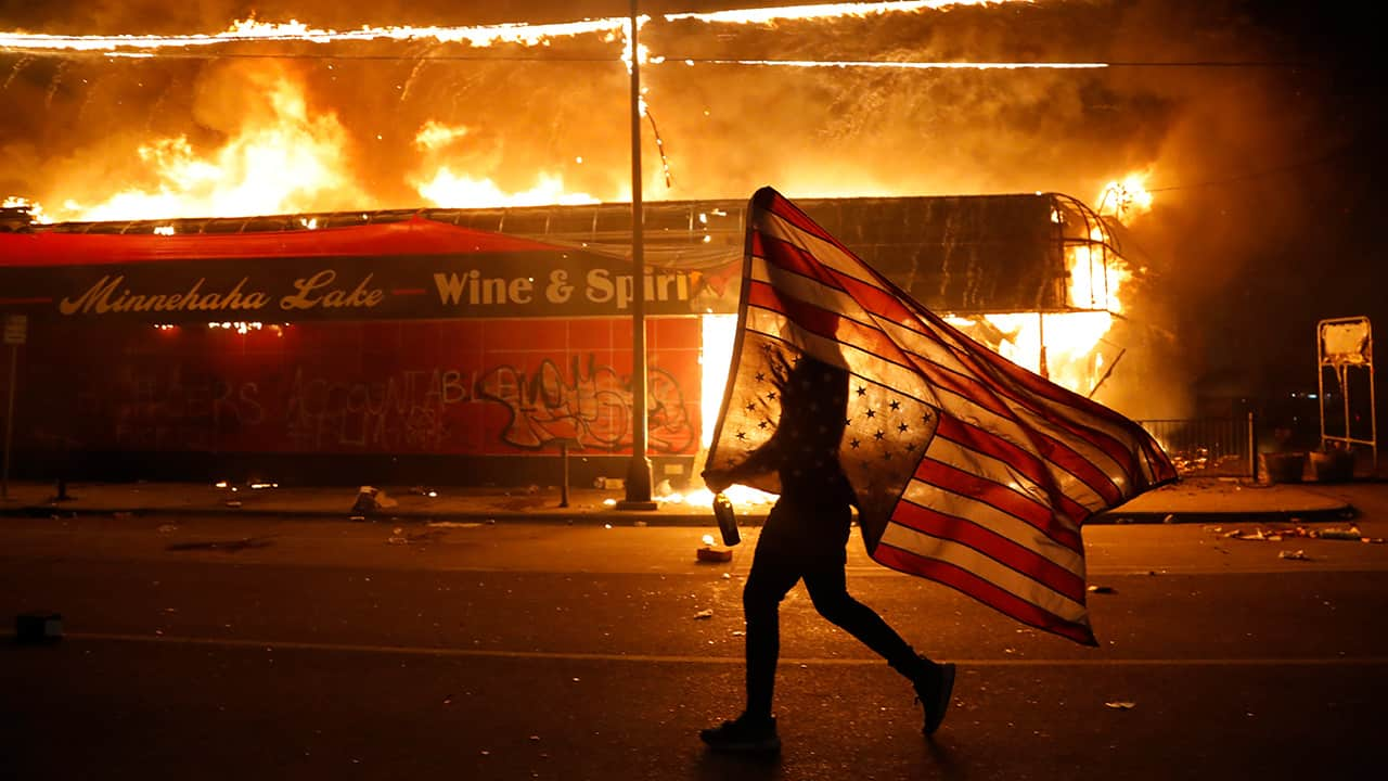 Photo of a protester carrying a flag upside down