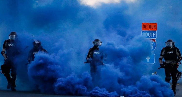 Photo of police officers in blue smoke