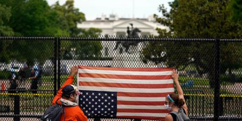 Photo of people holding a flag upside down at the white house
