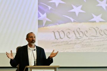 Photo of Andrew Fiala with an image of the U.S. Constitution in the background