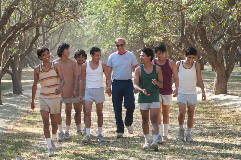 """Photo from The Disney film """"McFarland, USA"""" of cross country runners and their coach in an orchard"""