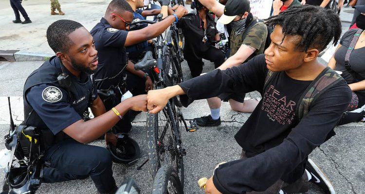 Photo of a police officer fist bumping a protester in Atlanta