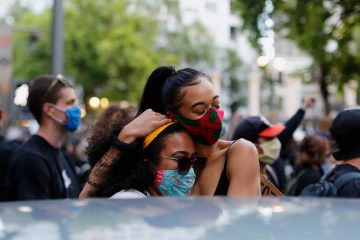 Photo of protesters hugging in Portland
