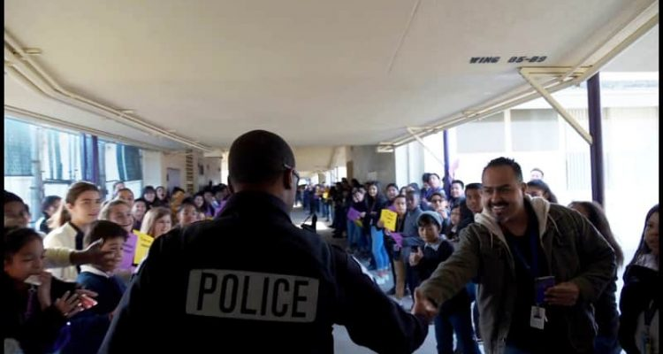 Photo of campus resource officer Martin saying goodbye to students at Cooper Academy in Fresno, Californiaooo