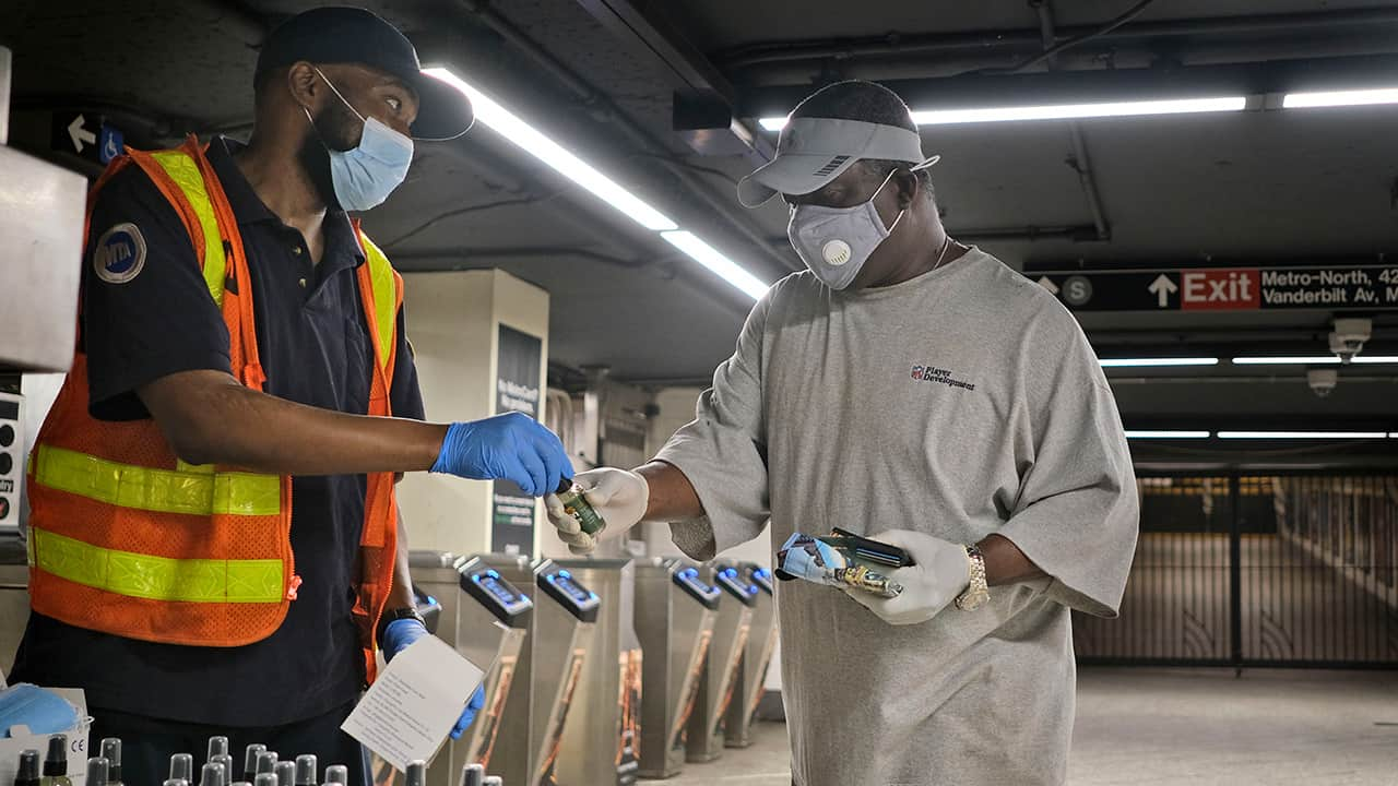 Photo of an MTA employee giving away masks and sanitizer