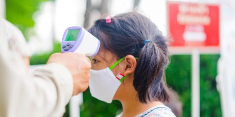 Photo of a face mask wearing student having her temperature checked