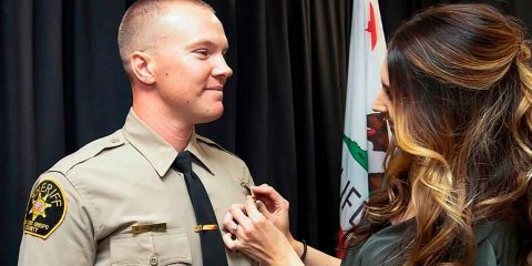 Photo of Deputy Nicholas Dreyfus receiving his badge from his wife