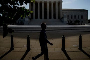 Photo fo a man walking past the Supreme Court