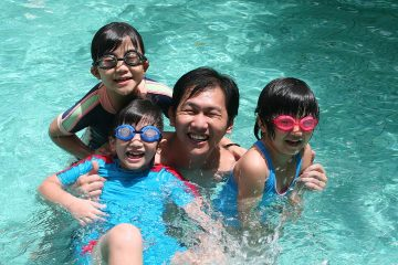 Photo of a dad with his children in a swimming pool on Father's Day