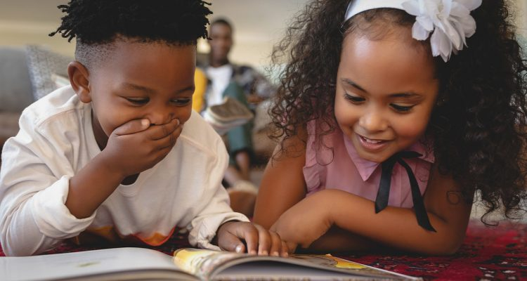 Image of two young African American students reading together