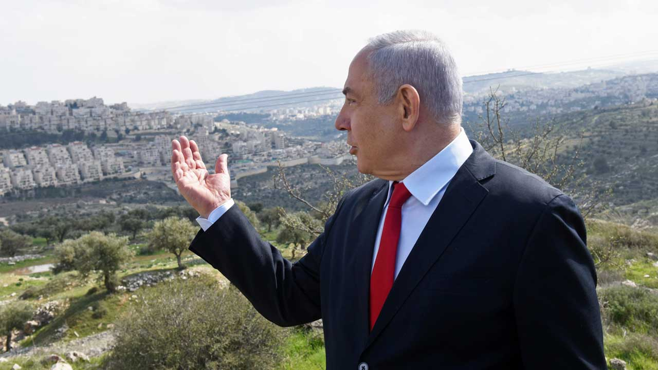 Image of Benjamin Netanyahu on a hill looking down on a West Bank neighborhood
