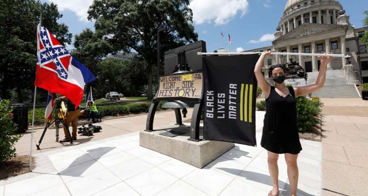 Photo of a woman holding a Black Lives Matter flag