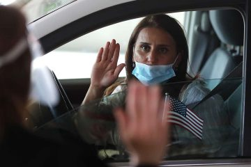 Photo of a woman during a drive-thru naturalization service
