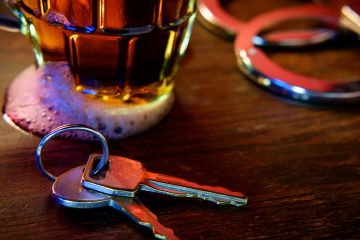 Image representing drunken driving: a beer glass, car keys, and handcuffs