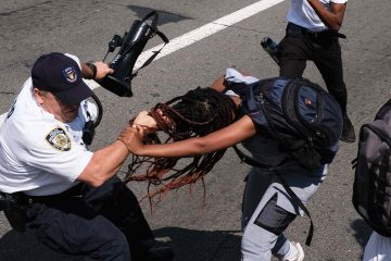 Photo of protesters struggling with an officer