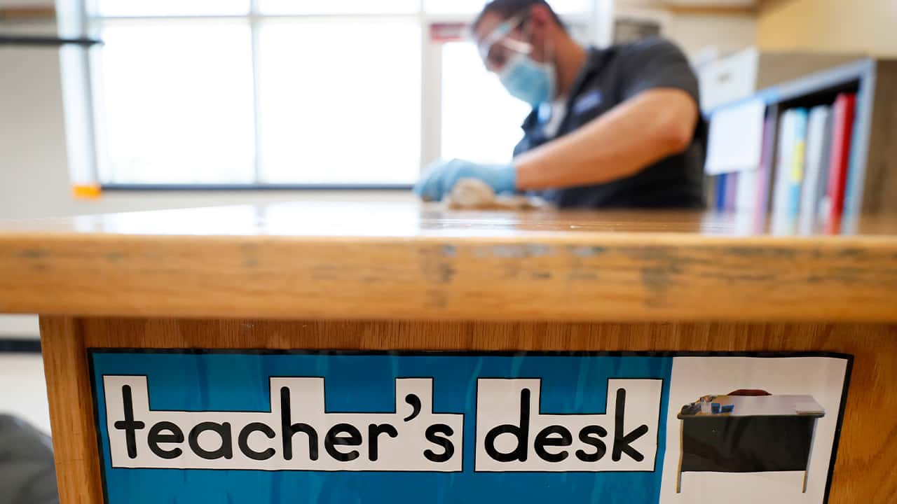 Image of a teacher's desk being sanitized in preparation for the reopening of schools during the coronavirus pandemic