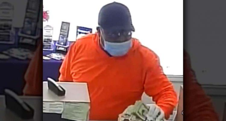Image of man wearing orange shirt and blue surgical mask robbing a bank in Easton, CaliforniaMan weari
