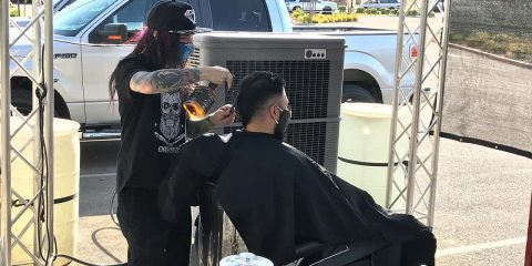Picture of barber giving a haircut outdoors during California's ordered shutdown because of the coronavirus pandemic
