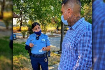 Image of a masked Fresno police officer talking to a masked resident