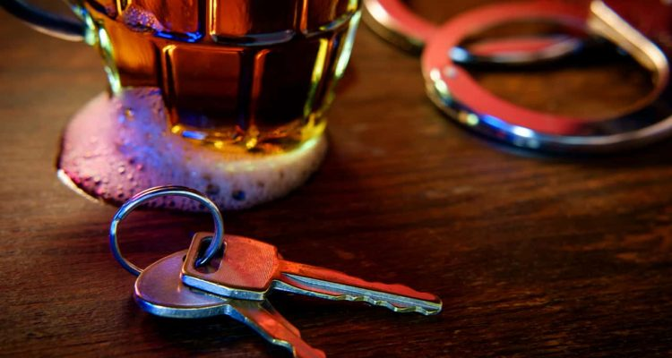 Image of a beer glass, handcuffs and car keys signifying drunken driving arrest
