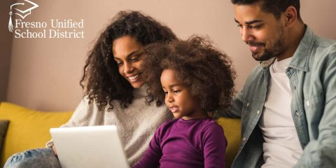 Image of Black parents checking out what their daughter is learning on her laptop
