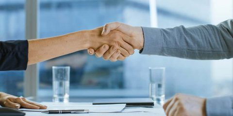 Image of a man and woman shaking hands symbolizing a business merger