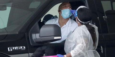 Image of a mobile COVID-19 test being given to a man in a car