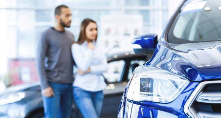 Photo of a man and woman shopping for a new car at a dealership