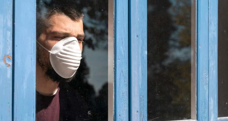 Image of a patient with a mask looking out of a hospital window