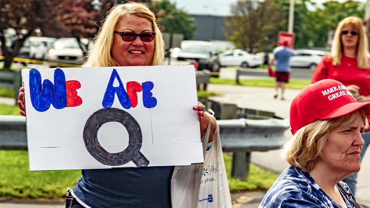 """Picture of a woman with a """"We are Q"""" sign at at a 2018 Make America Great Again rally in Wilkes-Barre, Pennsylvania"""