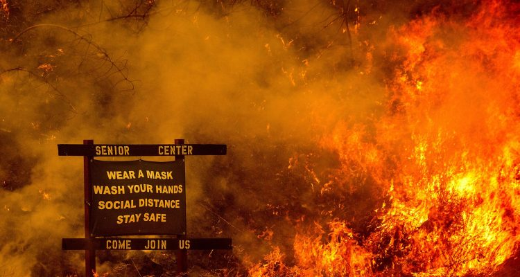 Photo of a sign for a senior center surrounded by wildfire flames