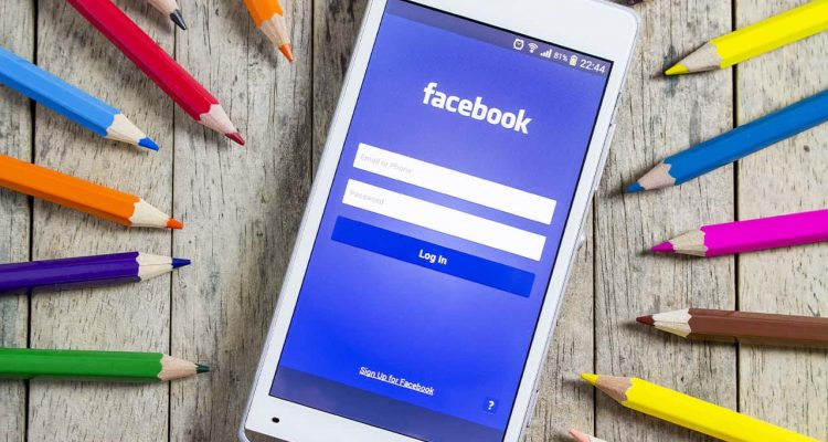 Photo of smartphone opened to Facebook sign-in page surrounded by colored pencils