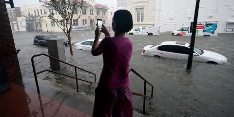 Photo of a woman taking photos of the flooding
